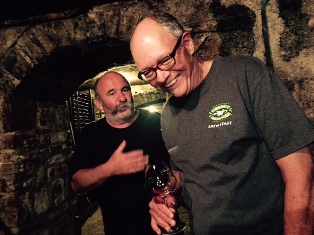 Scott and Thierry joking and tasting wine in cellar