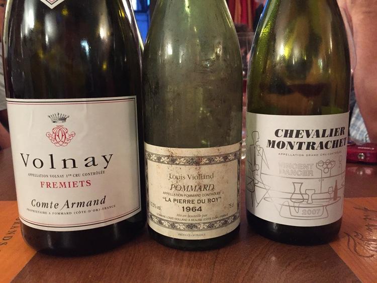 Three empty bottles of wine on table